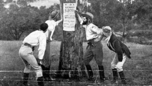 Kelly y su banda contemplan un cartel con la recompensa por su detención. © National Film and Sound Archive, Camberra, Australia (Archivo Nacional Audiovisual de Australia, consultado en: http://www.nfsa.gov.au/)